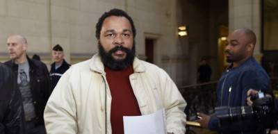 """French controversial comic Dieudonne M'bala M'bala (C) arrives at the Paris courthouse on March 12, 2015, for the trial of French far-right writer Alain Soral (L),  for posting a picture of himself on the internet taken in Berlin in front of the Memorial to the Murdered Jews of Europe, while gesturing the """"quenelle"""", a gesture viewed as anti-Semitic. The gesture, invented by French controversial comic Dieudonne M'bala M'bala, is viewed as anti-semitic, while Dieudonne and his supporters claim it is anti-establishment.   AFP PHOTO / LOIC VENANCE / AFP / LOIC VENANCE"""